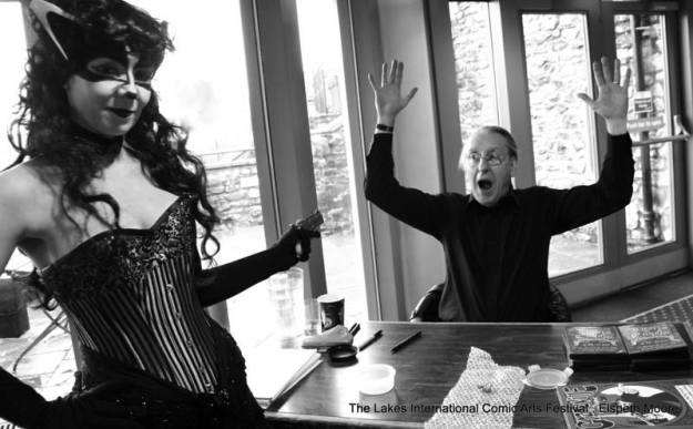 Our very own Billie-alike Maisie Stevenson holds Bryan at gunpoint...